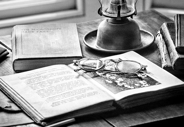 closeup image of an old open book with eyeglasses on it, with an old lamp and books at the back