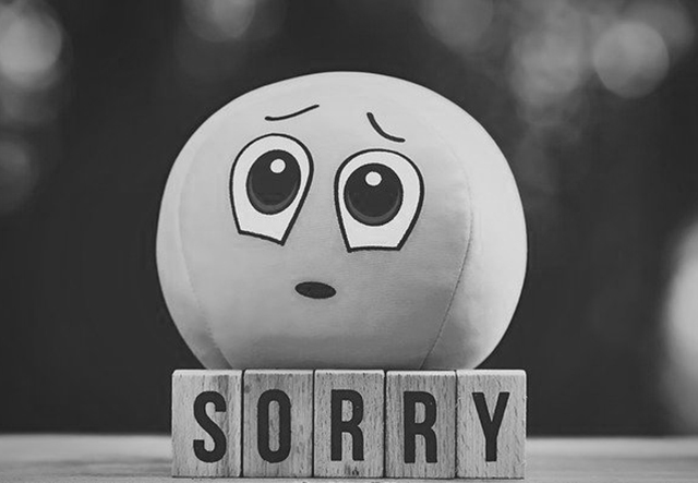 tiles spelling the word sorry, on top of it is a ball with sorry face