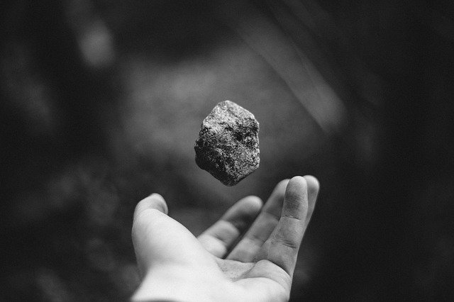 hand held out with a floating rock above it, representing useless inventions