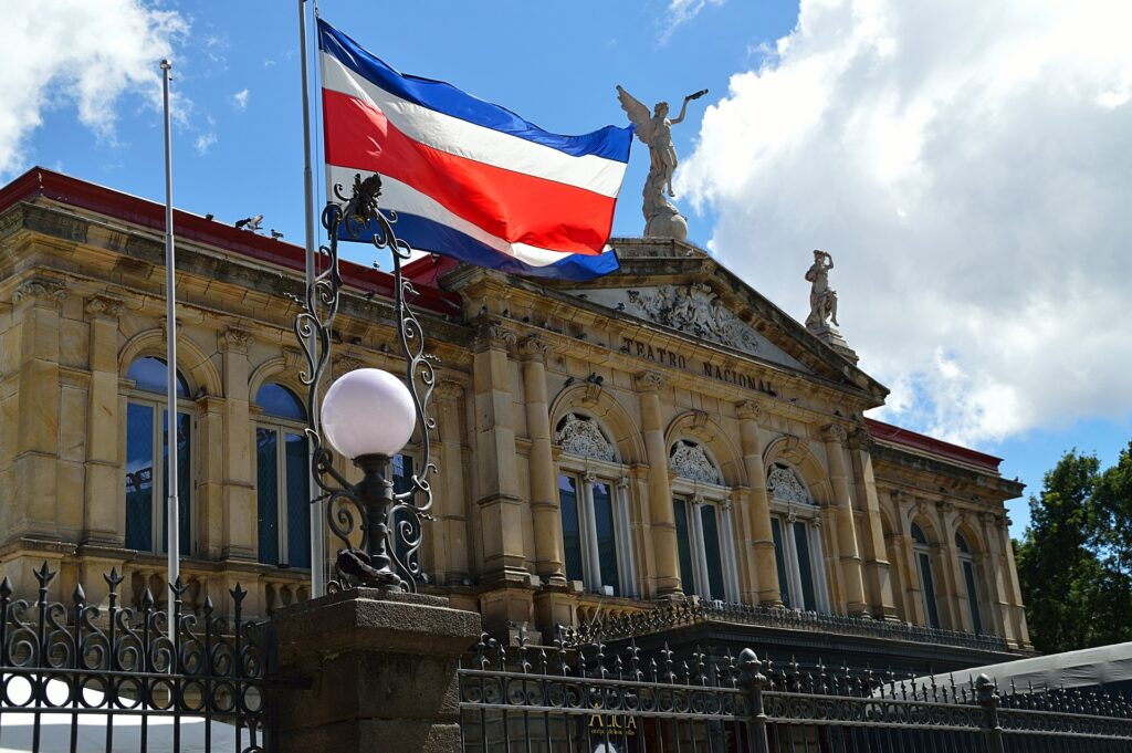 an image with the Costa Rica's flag raised in a pole in front of the Teatro Nacional building